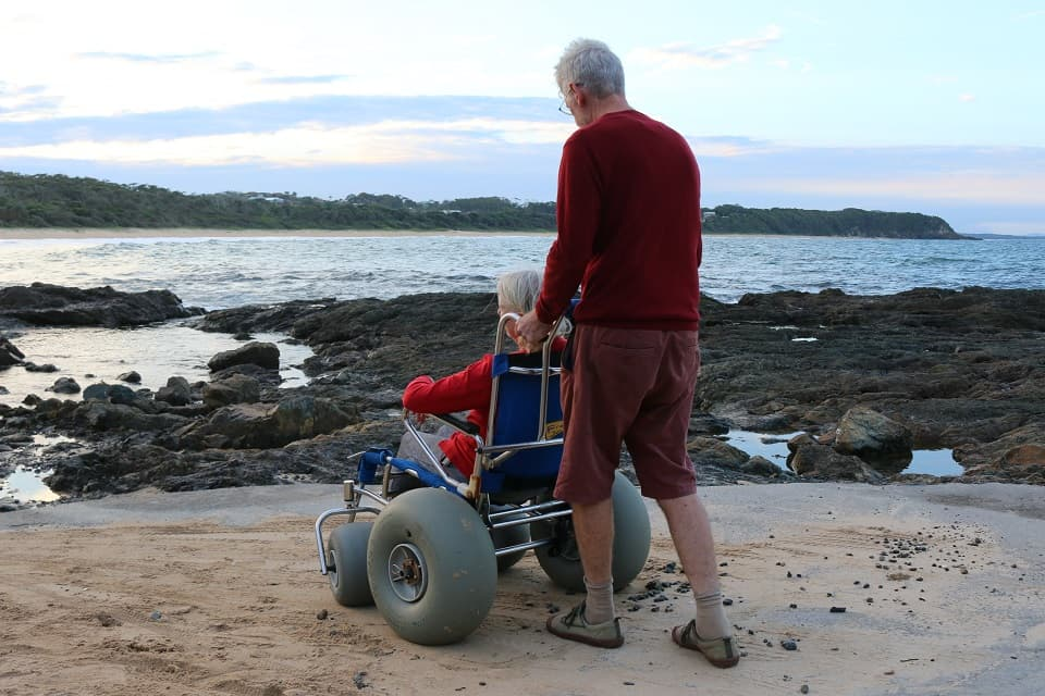 wheelchair user at black head beach