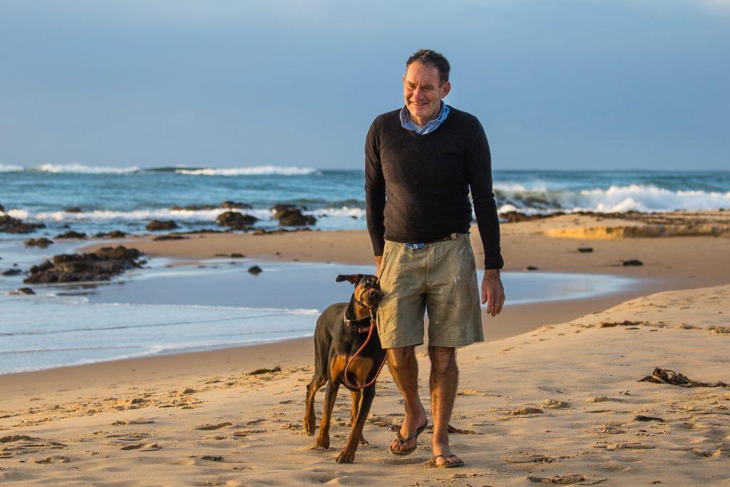 Man walking dog on dog friendly beach